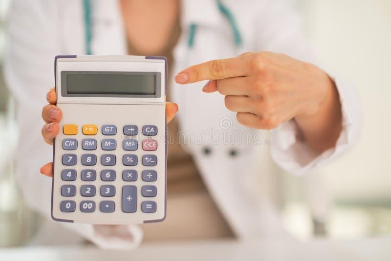 Primer en la mujer del doctor que señala en la calculadora foto de archivo libre de regalías