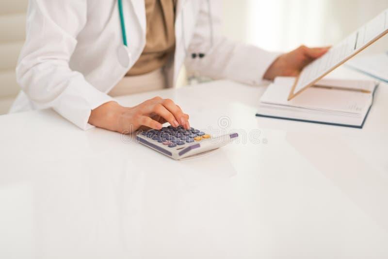 Primer en la mujer del médico que usa la calculadora imagenes de archivo
