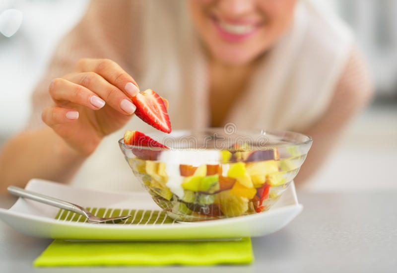 Primer en la mujer feliz que sirve la ensalada de fruta fresca fotografía de archivo libre de regalías