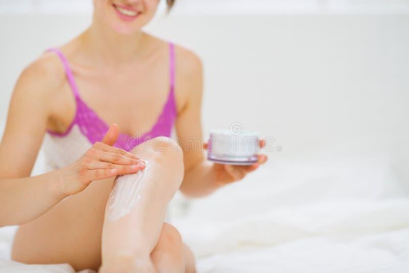 Primer en la mujer que aplica la nata en la pierna en cama fotos de archivo libres de regalías