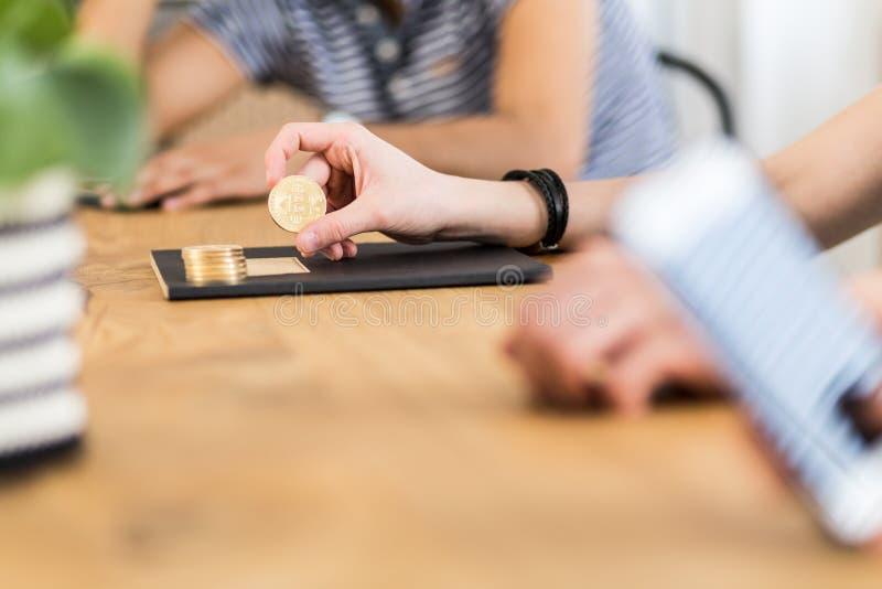 Primer en la persona que sostiene la moneda de oro de Bitcoin - símbolo del virt fotos de archivo