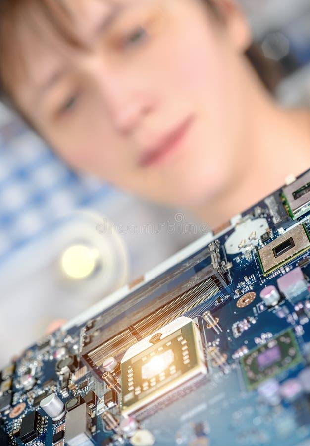 Primer en la placa madre observada por una tecnología femenina fotografía de archivo libre de regalías