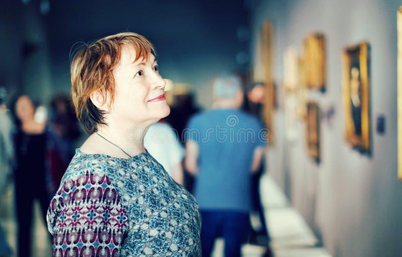 Primer en museo que visita de la mujer mayor atenta y a del goce imágenes de archivo libres de regalías