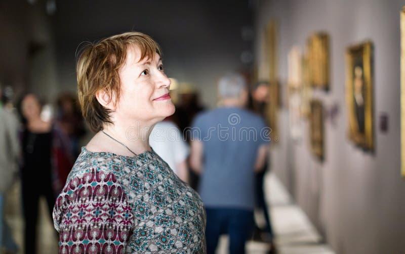 Primer en museo que visita de la mujer mayor atenta y a del goce fotografía de archivo