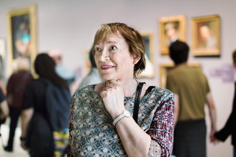 Primer en museo que visita de la mujer mayor atenta y a del goce fotos de archivo