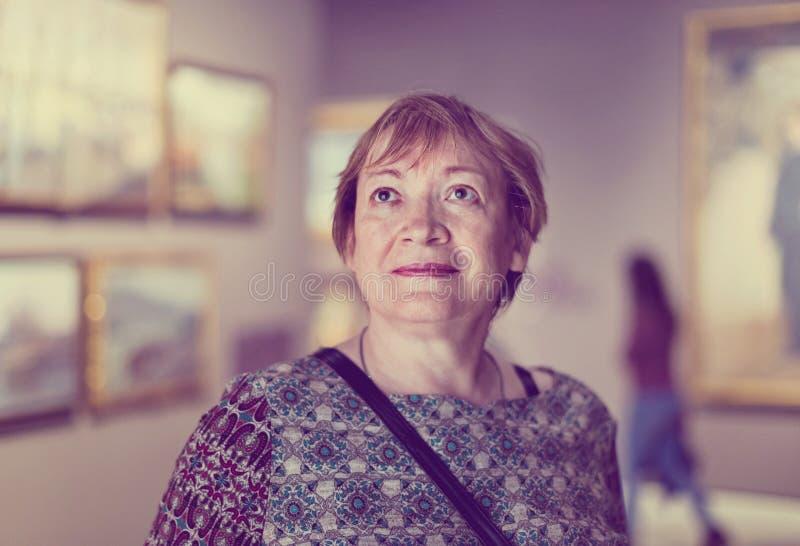 Primer en museo que visita de la mujer mayor atenta y a del goce imagenes de archivo