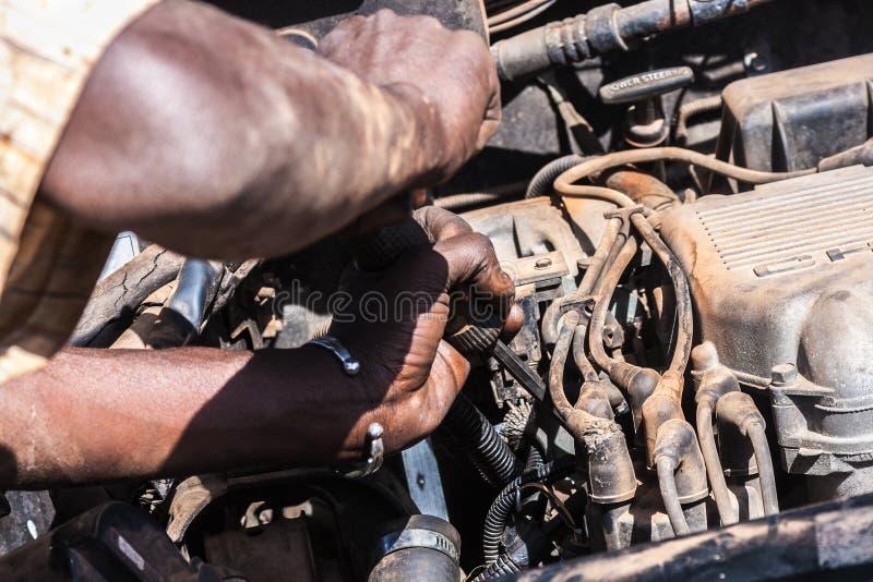 Primer en un hombre africano que trabaja en un motor de coche quebrado imagen de archivo libre de regalías