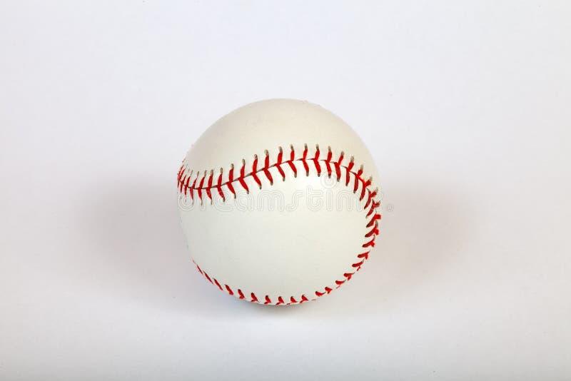 Primer en una bola blanca del béisbol cosida con el hilo grueso rojo hecho del cuero auténtico para el juego de equipo americano  fotografía de archivo