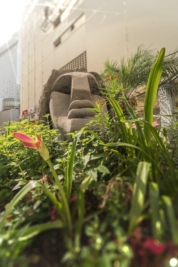 Primer en una estatua de una cabeza de Moai rodeada por el flowe tropical imágenes de archivo libres de regalías