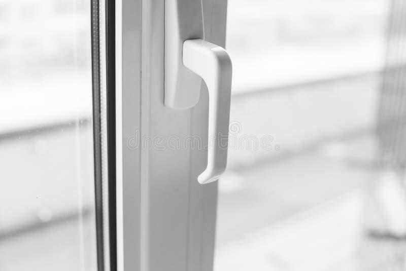 Primer en una manija blanca de la ventana del pvc foto de archivo