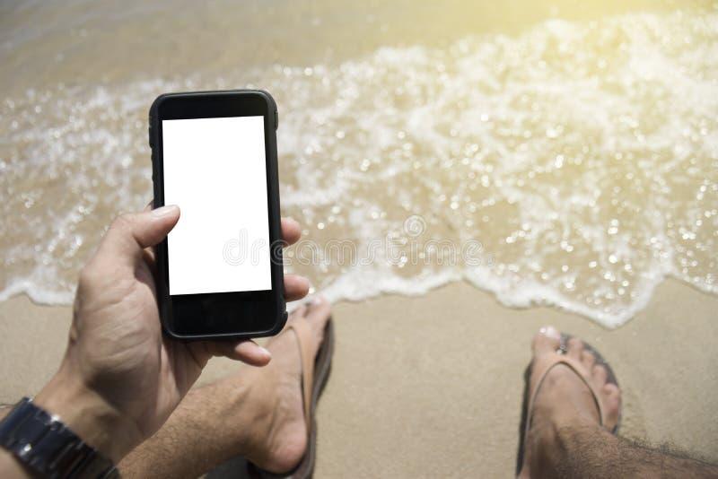 Primer en una mano del hombre que sostiene el teléfono elegante en la playa colocación en la playa fondo exterior Día asoleado Fo imágenes de archivo libres de regalías