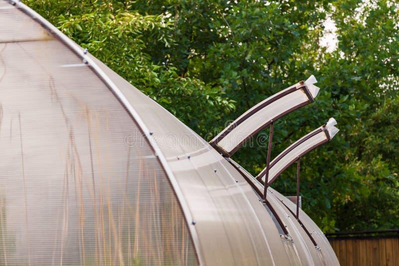 Primer en ventanas abiertas en un invernadero construido del policarbonato y del plástico para la ventilación del aire caliente y imagen de archivo libre de regalías