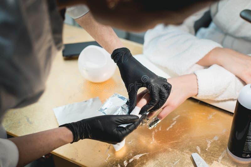 Primer esmalte de uñas de Removing del manicuro de un viejo con un poco de acetona foto de archivo