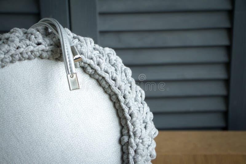 Primer extremo de un bolso hecho punto hecho a mano detalladamente Bolso gris con la parte inferior y las correas de cuero foto de archivo libre de regalías