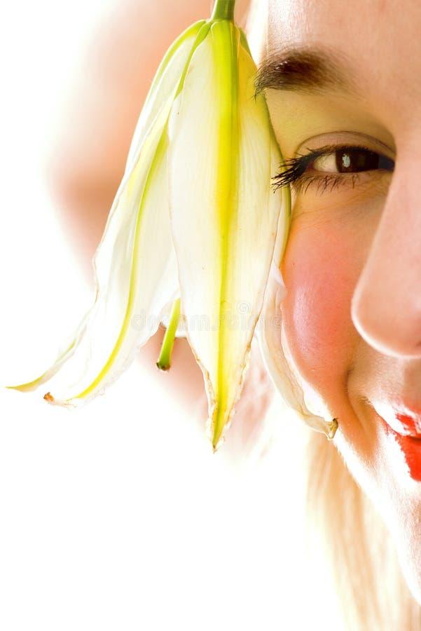 Primer femenino sonriente de la cara con el lirio fotografía de archivo