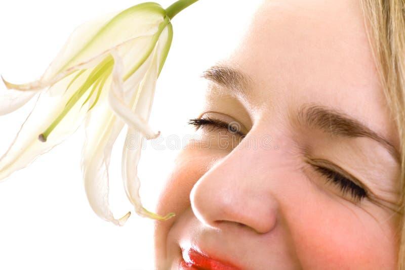 Primer femenino sonriente de la cara con el lirio imagenes de archivo