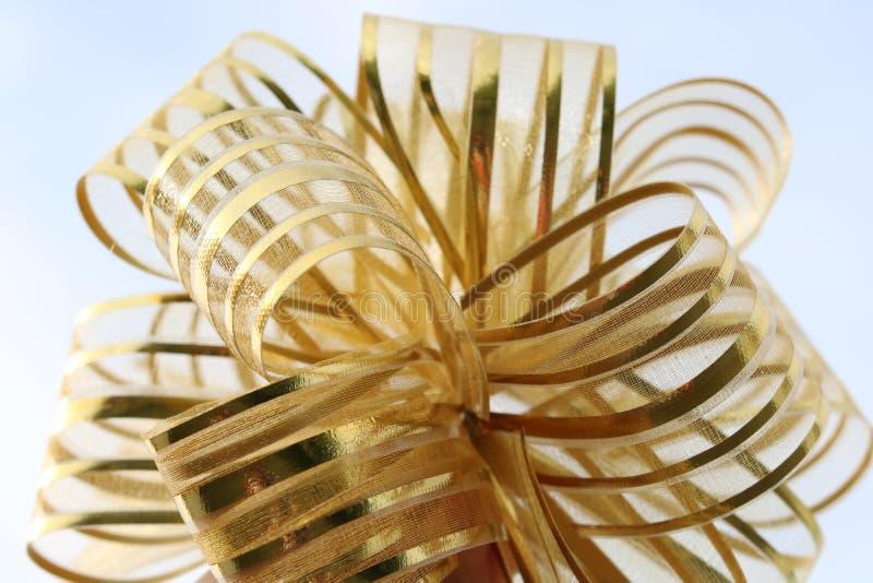 Primer festivo de oro del arco en fondo azul fotos de archivo libres de regalías