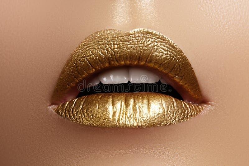 Primer hermoso con los labios regordetes femeninos con maquillaje del color oro La moda celebra el maquillaje, cosmético del bril imagen de archivo libre de regalías