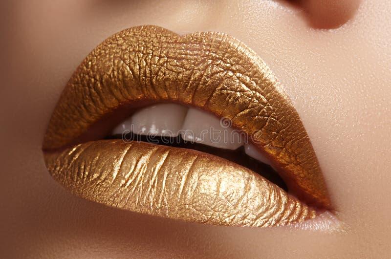 Primer hermoso con los labios regordetes femeninos con maquillaje del color oro La moda celebra el maquillaje, cosmético del bril foto de archivo