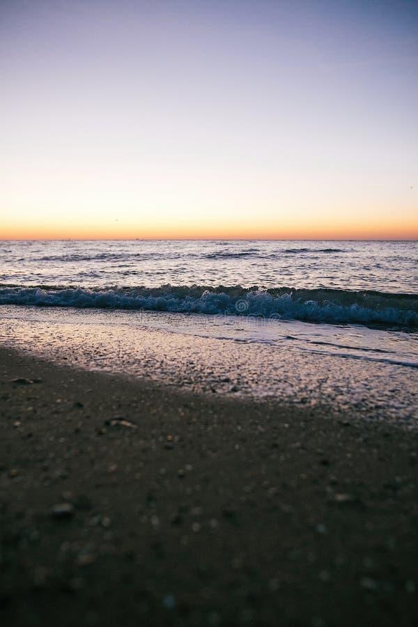 Primer hermoso de la espuma de las ondas del mar y playa arenosa con las conchas marinas en luz de la salida del sol en la isla t imagenes de archivo