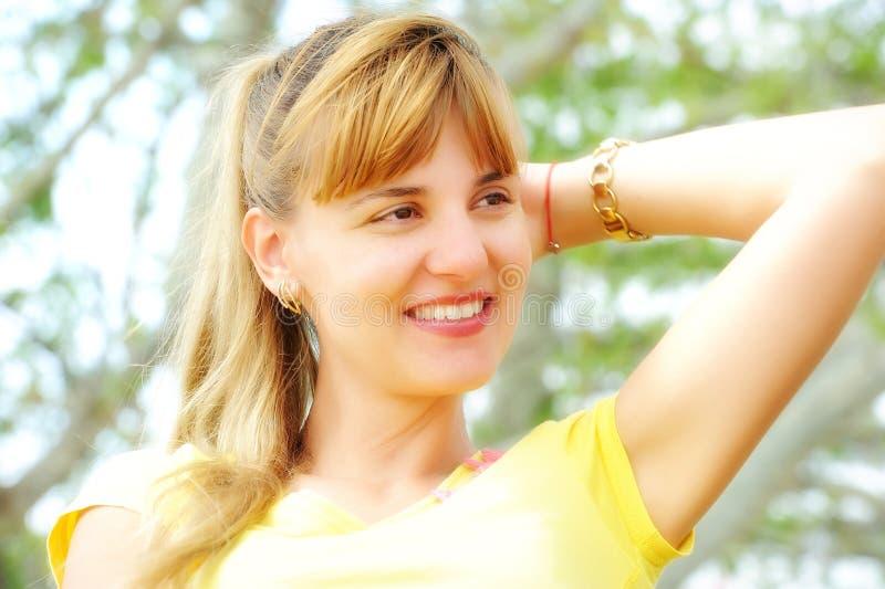 Primer hermoso de la mujer joven en suéter anaranjado, contra verde fotografía de archivo
