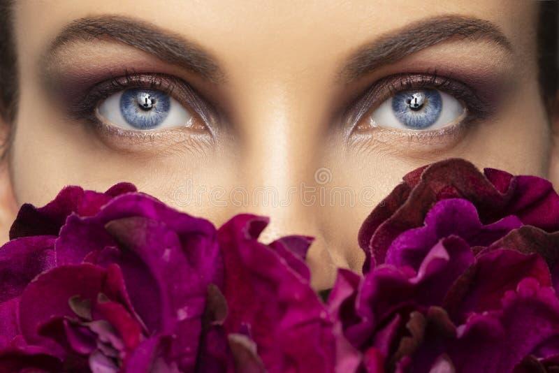 Primer hermoso de los ojos humanos Lanzamiento macro de los ojos azules de la mujer joven Ojo macro del primer con las flores de  foto de archivo libre de regalías