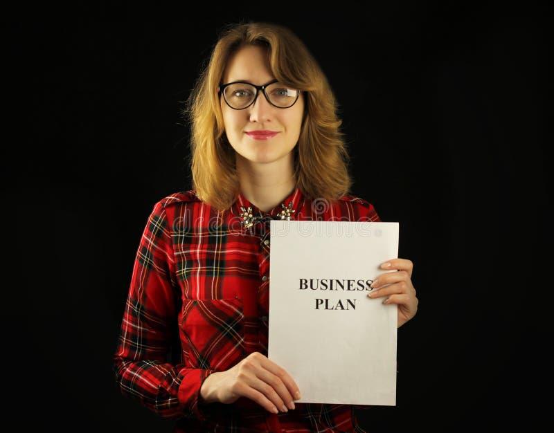 Primer hermoso joven de la muchacha en una camisa a cuadros roja que se sostiene de papel en sus manos con un plan empresarial pa imagen de archivo libre de regalías
