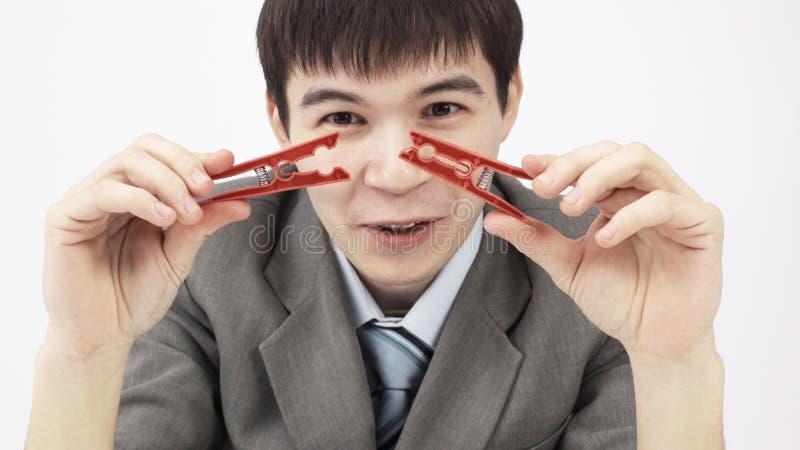 primer hombre de negocios joven que sostiene dos pinzas, sent?ndose detr?s de un escritorio imagen de archivo