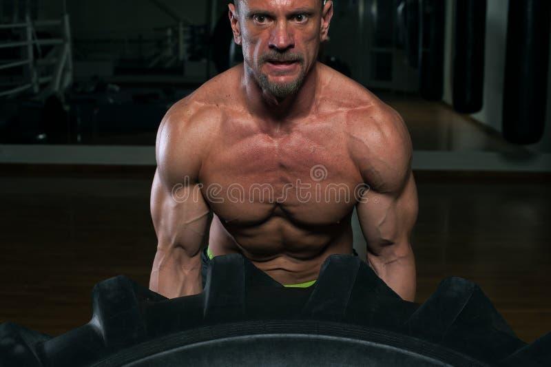 Primer - hombre fuerte muscular que levanta el neumático pesado fotos de archivo