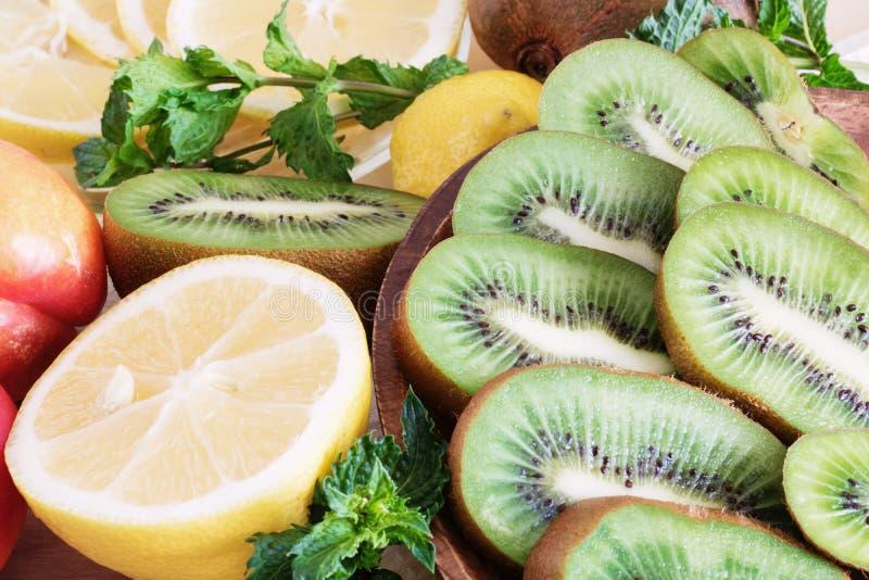 Primer jugoso de la fruta, comidas sanas, ingredientes de la dieta, rebanadas del kiwi cerca del limón y melocotones jugosos cerc fotos de archivo