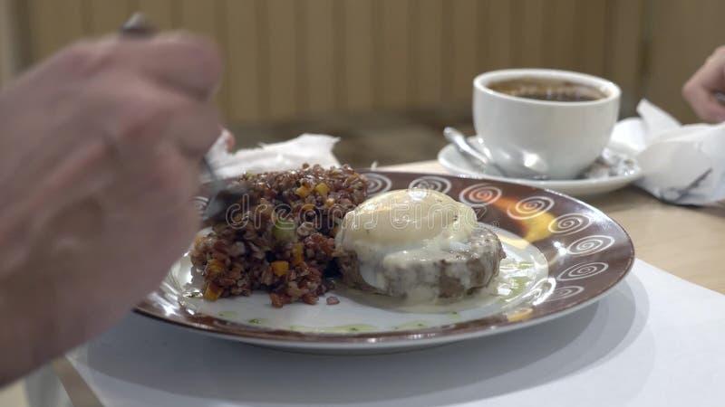 Primer 4K el hombre come el arroz rojo con el filete y el huevo de carne de vaca escalfados, con las verduras fotos de archivo