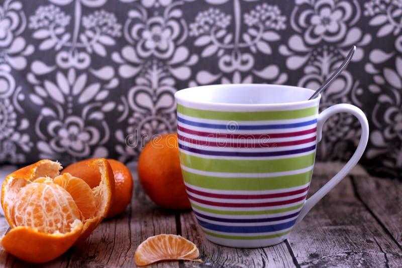 Primer a la taza de infusión de hierbas con el tangerineson, en una tabla de madera Bebida de la salud en los meses de invierno P imagen de archivo