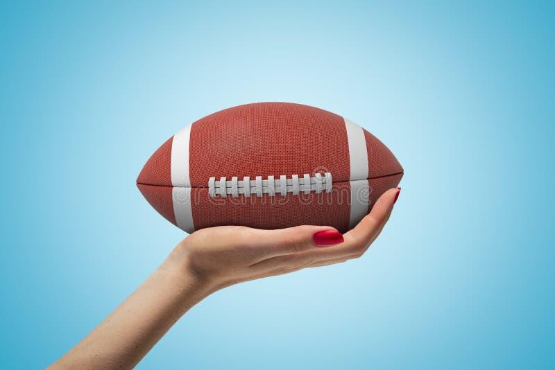 Primer lateral de la mano de la mujer que hace frente para arriba y que sostiene la bola marrón grande para el fútbol americano e imagen de archivo libre de regalías