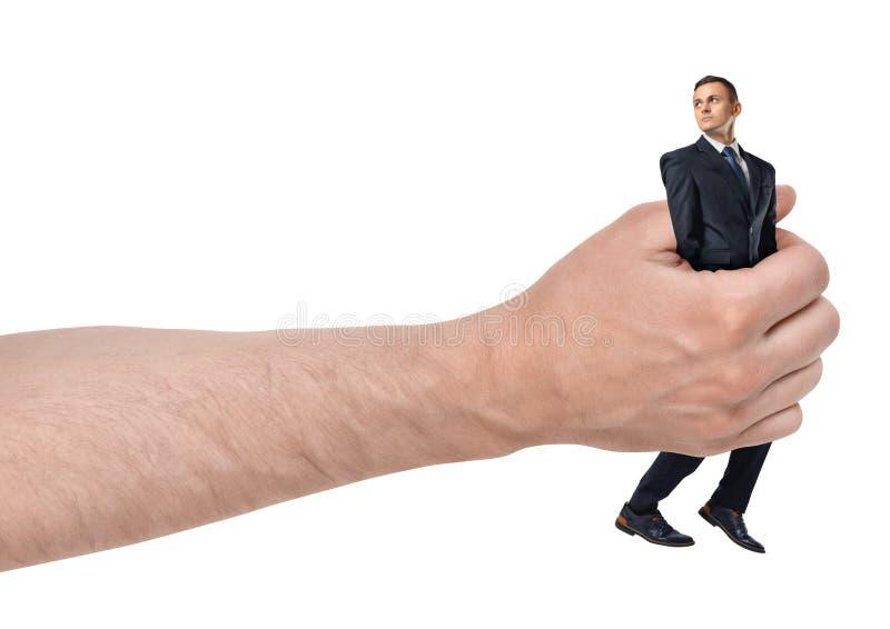 Primer lateral hombre de negocios de la tenencia de la mano del hombre grande del pequeño aislado en el fondo blanco fotos de archivo libres de regalías