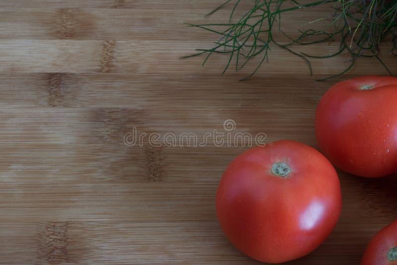 Primer maduro de los tomates en un fondo de madera, foto de archivo