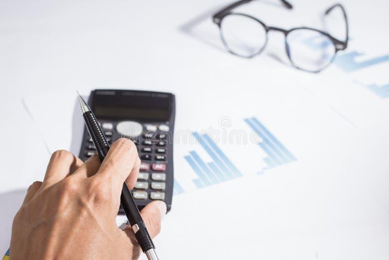 Primer Mano de la calculadora de trabajo del negocio o de la cuenta, beneficio o econom?a del gr?fico en Ministerio del Interior imagen de archivo
