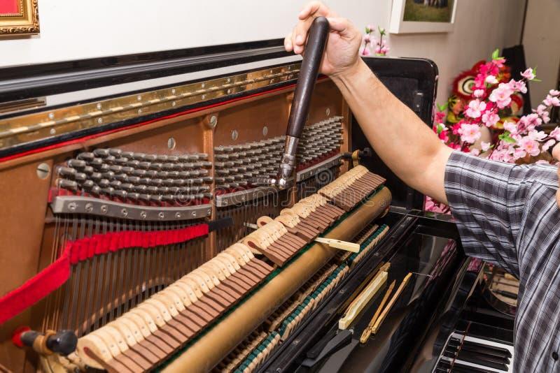 Primer a mano que adapta un piano vertical usando palanca y las herramientas fotos de archivo