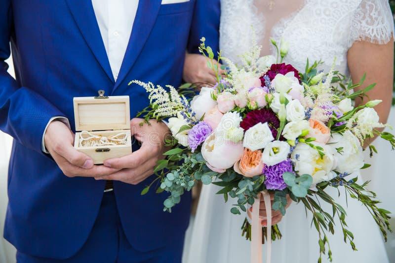 Primer Manos de la novia y del novio que sostienen el ramo y caja con los anillos en ataúd fotografía de archivo libre de regalías