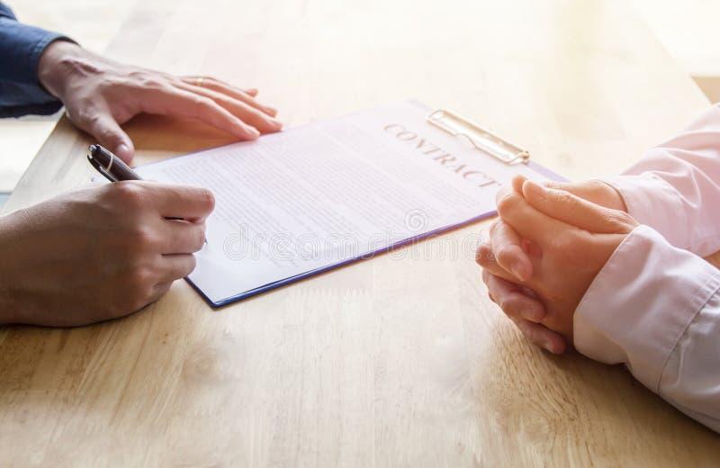 Primer Negocio asiático de la pluma de tenencia de la mano que revisa y que firma, contrato casero de la compra imagenes de archivo