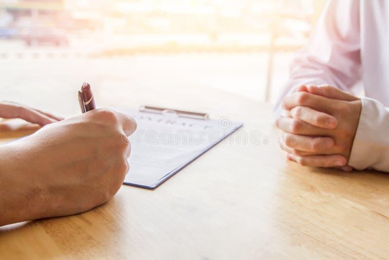 Primer Negocio asi?tico de la pluma de tenencia de la mano que revisa y que firma, contrato casero de la compra, foco selectivo imagen de archivo