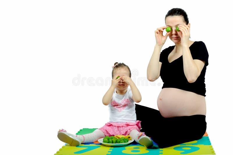 Primer niño aislado que juega a su madre embarazada con las frutas imagen de archivo libre de regalías