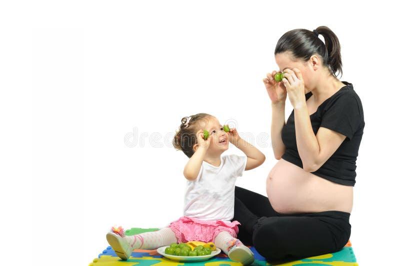 Primer niño aislado que juega a su madre embarazada con las frutas en blanco imagenes de archivo