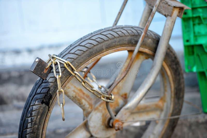 Primer photography Una rueda delantera de la motocicleta vieja se cierra en la cadena del hierro fotografía de archivo