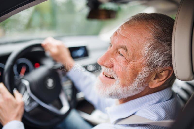 Primer plano del feliz anciano sentado en el asiento del conductor, conduciendo fotografía de archivo