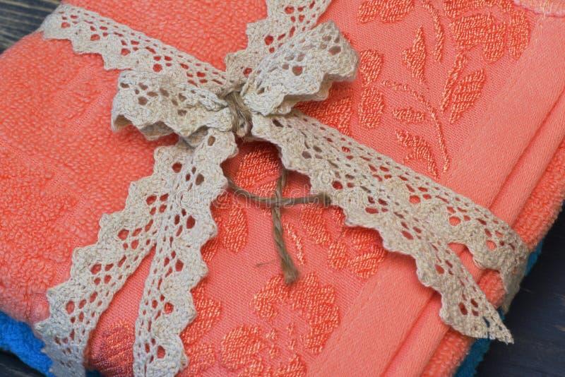 Primer Presente Toallas del algodón atadas con la cinta a cielo abierto y el arco a cielo abierto en fondo de madera natural oscu imagenes de archivo