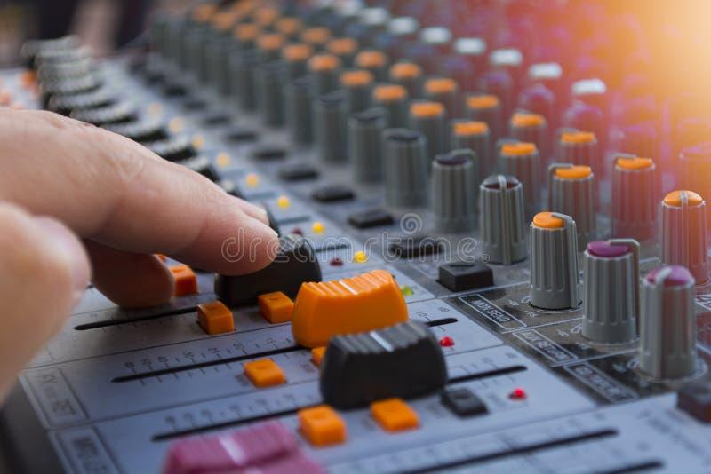 Primer profesional del mezclador de sonidos de la etapa en la mano del ingeniero de sonido usando el resbalador audio de la mezcl foto de archivo libre de regalías