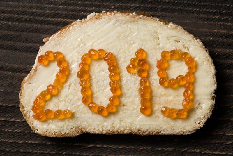 Primer puesto plano del bocadillo con el texto 2019 hecho del caviar rojo foto de archivo libre de regalías