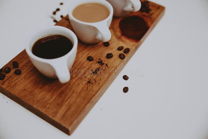 Primer tirado de diversos tipos de café en una bandeja de madera y una superficie blanca foto de archivo libre de regalías