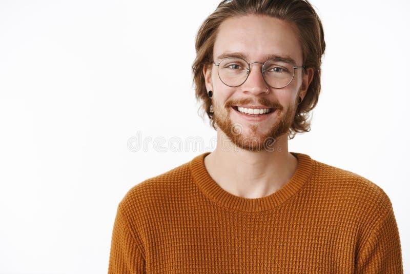 Primer tirado de encantar clase carismática y al varón feliz con la barba y vidrios en suéter caliente que sonríen ampliamente en fotos de archivo
