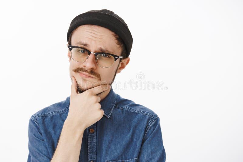 Primer tirado de individuo joven hermoso sospechoso elegante dudoso con la barba y del bigote en gorrita tejida y vidrios negros fotografía de archivo libre de regalías